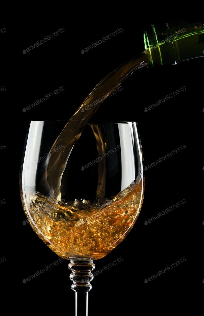Gießen Wein in Glas isoliert auf schwarz