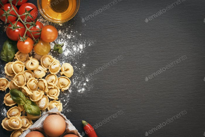 Fresh tortellini pasta and ingredients on a dark board