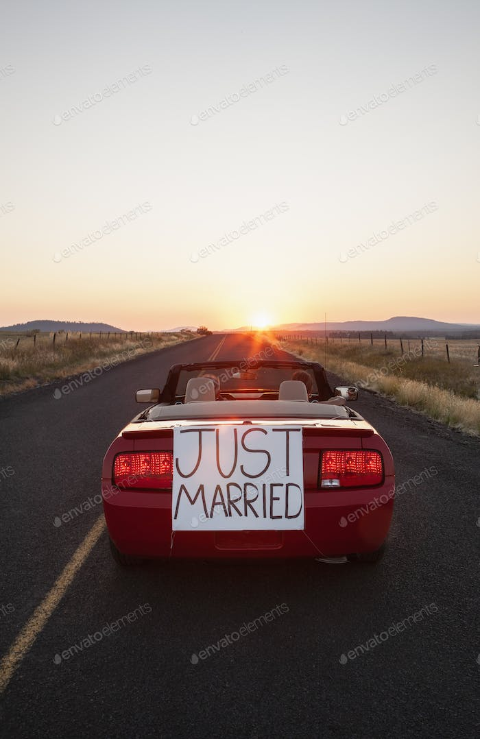 "A senior couple ""just married"" riding in a convertible sports car in eastern Washington State, USA."