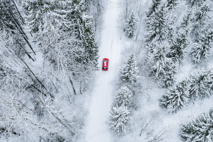 Aerial top view of snow covered forest with winter road and red car.