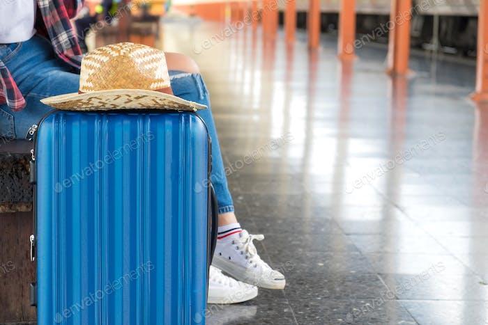 Touristen warten auf den Zug mit Gepäck auf der Seite.
