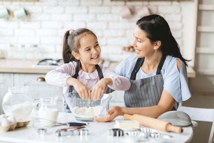 Cheerful daughter and mother in aprons cooking together in kitchen