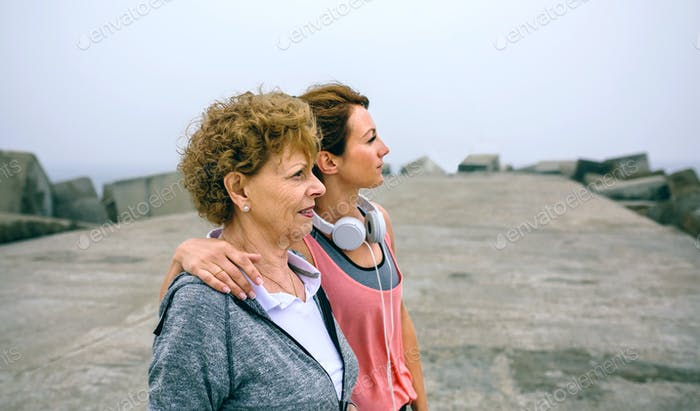 Senior and young sportswoman looking away