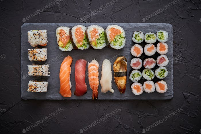 Sushi rolls set with salmon and tuna fish served on black stone board