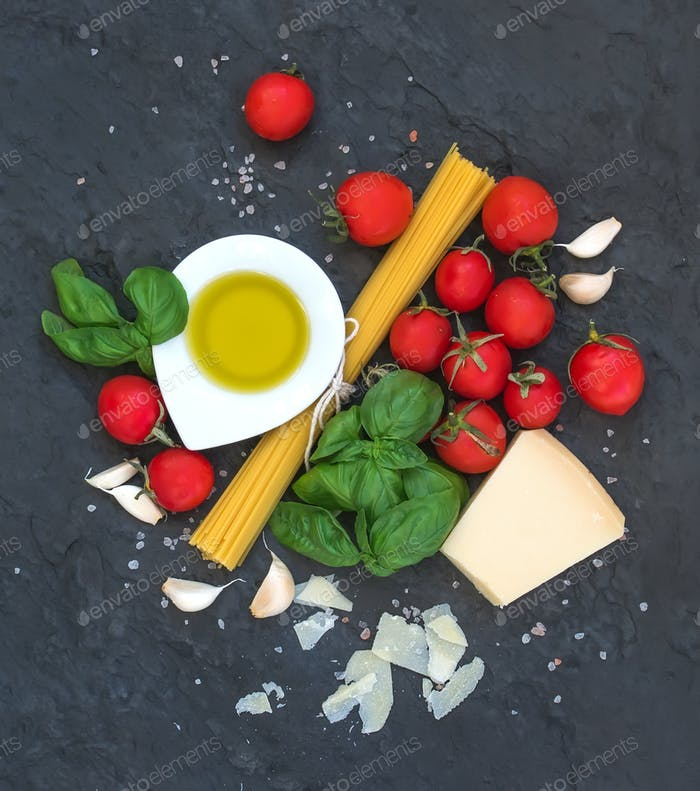 Ingredients for cooking pasta. Spaghetti, olive oil, garlic, Parmesan cheese, tomatoes