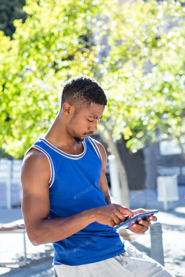 Smiling athletic man using tablet computer in the city
