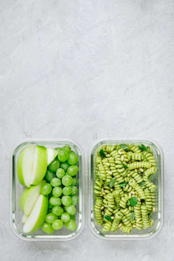 Vegetarian meal prep containers green pesto pasta. Apple and grape for dessert.