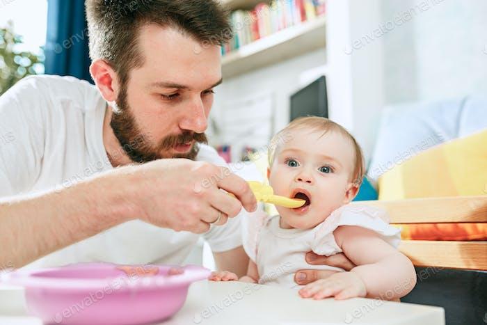 Gut aussehender junger Mann Essen Frühstück und Fütterung ihr Baby Mädchen zu Hause