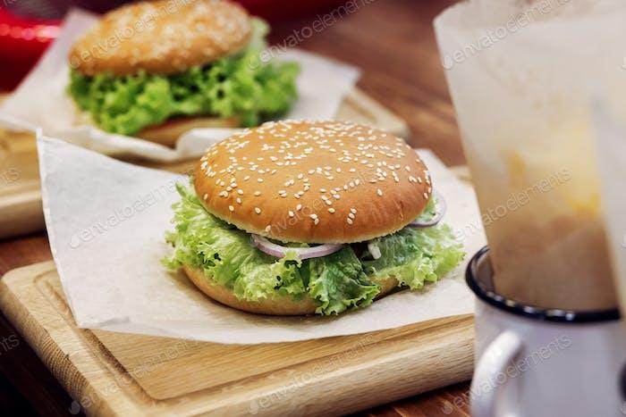 Yummy burger. serving cheeseburger or hamburger with salad on wooden desk