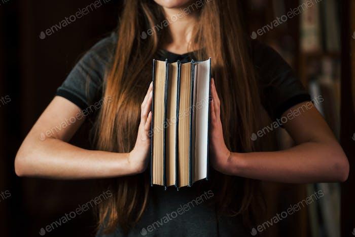 Hält viele Bücher in den Händen. Studentin ist in der Bibliothek. Konzeption der Bildung