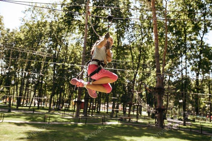 Little brave girl on zipline in rope park