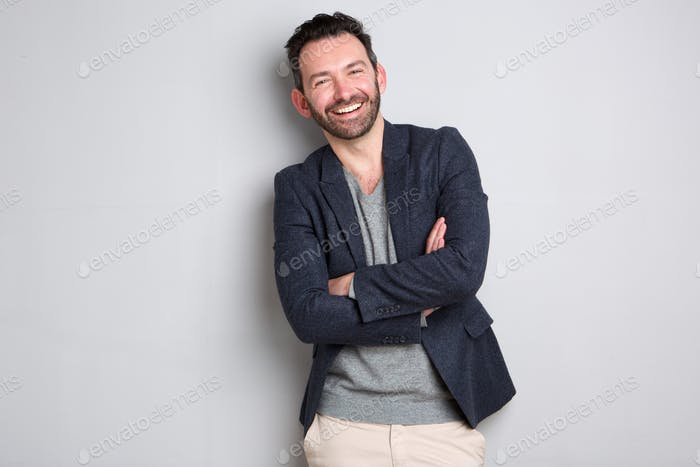 handsome man with beard laughing with arms crossed against gray background