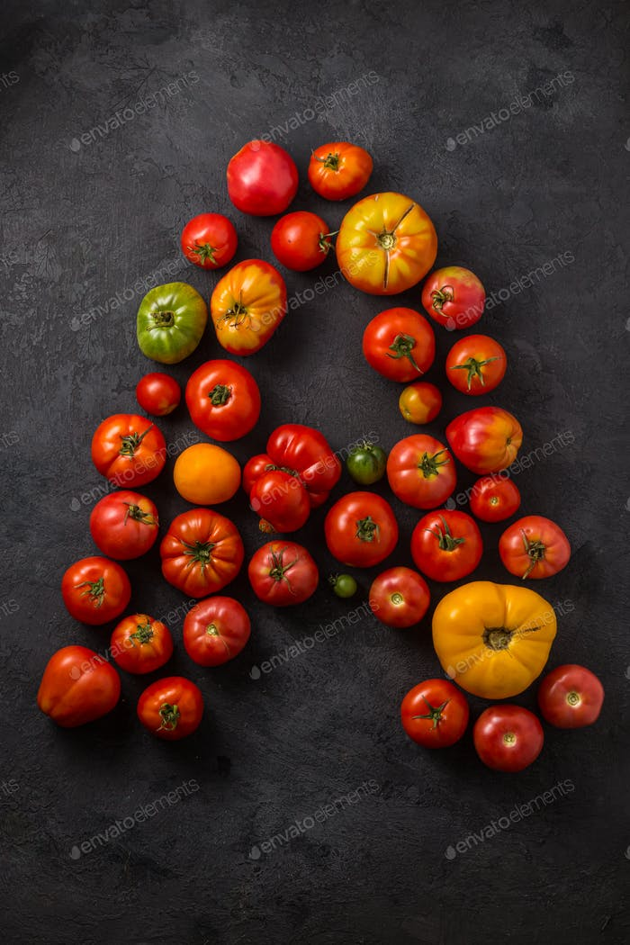 Letter A made with ripe tomatoes on a black background, creative flat lay healthy food concept