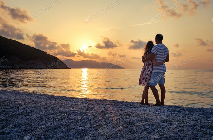 Young couple in love sitting on the beach