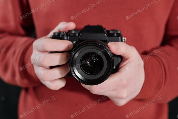 Hands of young male photographer in maroon sweatshirt holding new photocamera