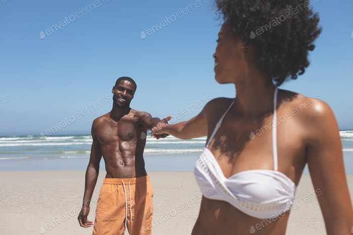 Portrait of handsome African-American man holding hand of mixed-race woman at beach on a sunny day