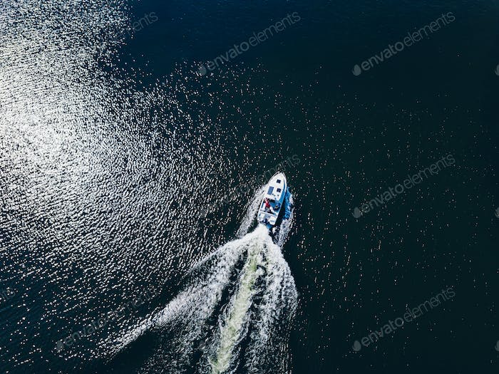 Aerial view of speed Boat or yacht at blue sea or lake leaving a wake