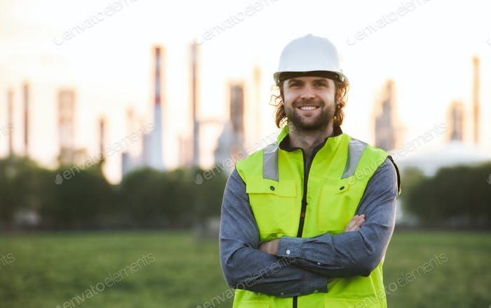 Young engineer standing outdoors by oil refinery, looking at camera