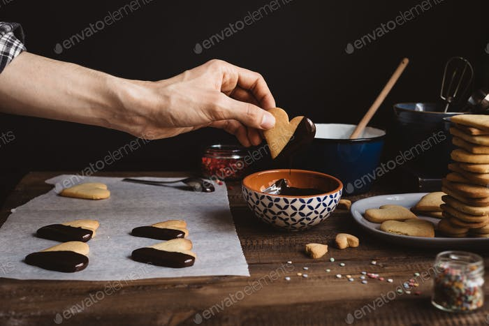 Man baking Chocolate Biscuits on Rustic Kitchen Table