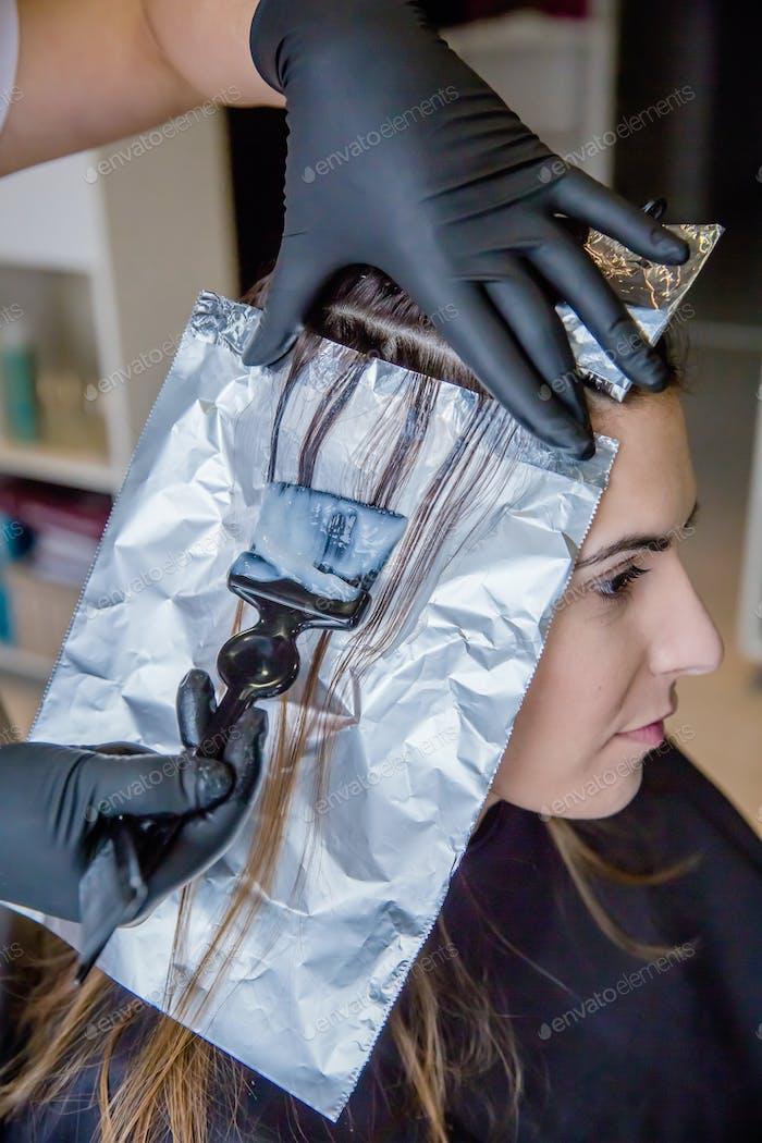 Closeup of hairdresser hands applying hair dye to client