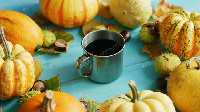 Metal cup of coffee with pumpkins