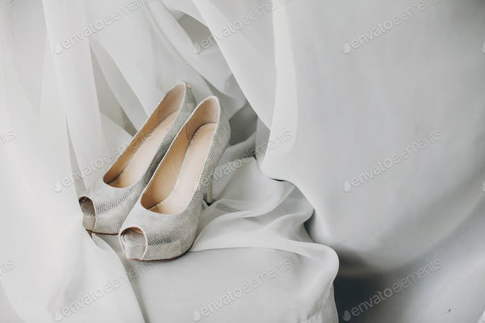 Stylish white shoes for bride on white tulle in soft morning light in hotel room