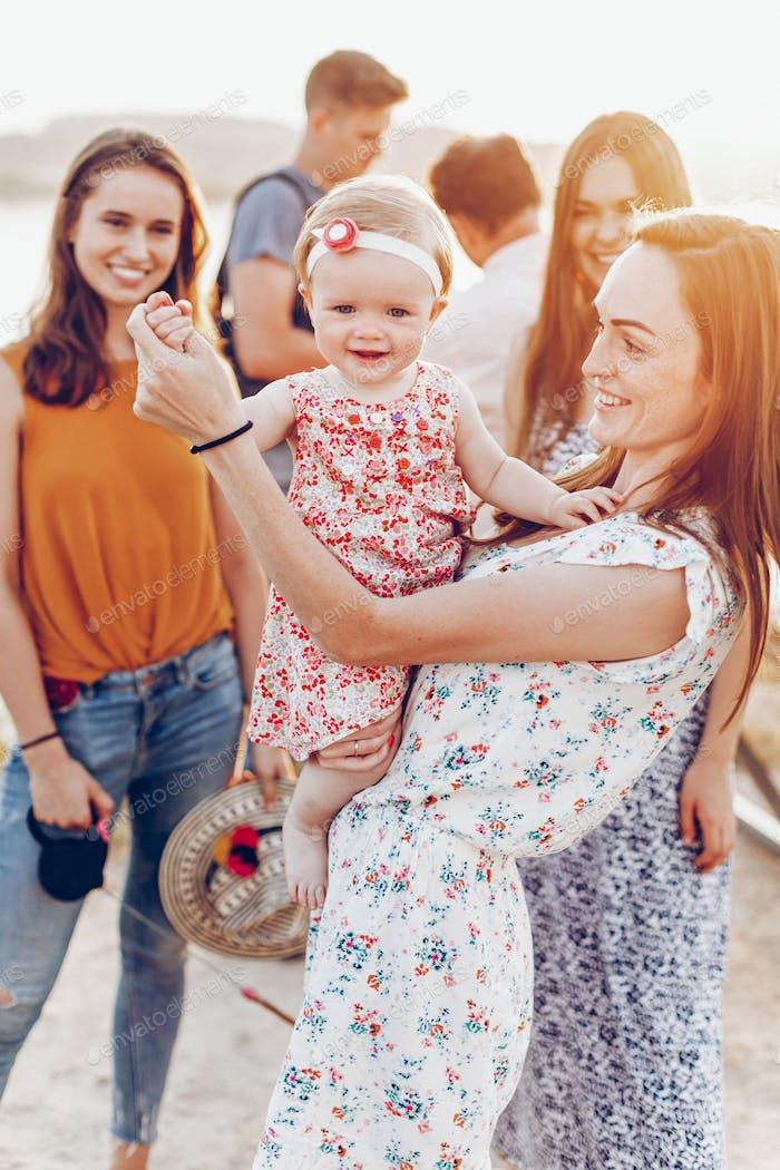 Happy stylish mom playing with joyful daughter and cuddling