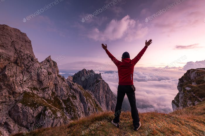 Happy Active Man at High Mountains Peak at Sunrise