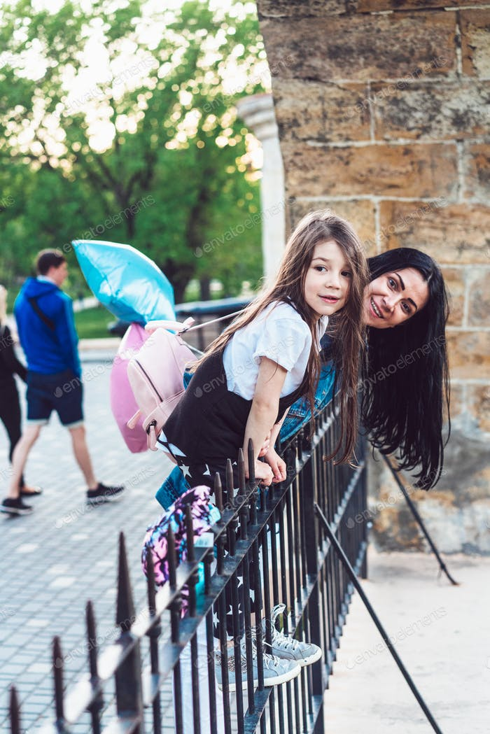 preschool girl and mother at the fence