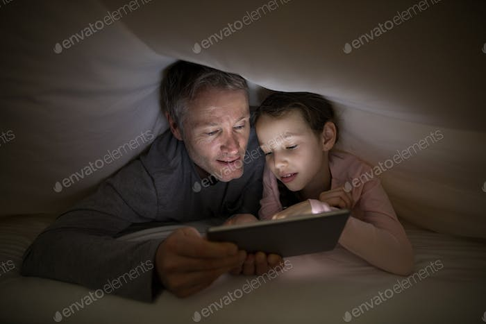 Father and daughter using digital tablet under blanket on bed