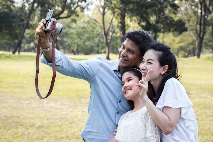 Asian families are taking family photos in a public garden.