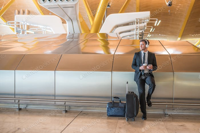 businessman at the airport listening music using his mobile phone waiting his flight