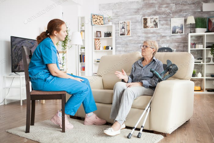 Nurse on a chair in a nursing home talking with elderly age woman