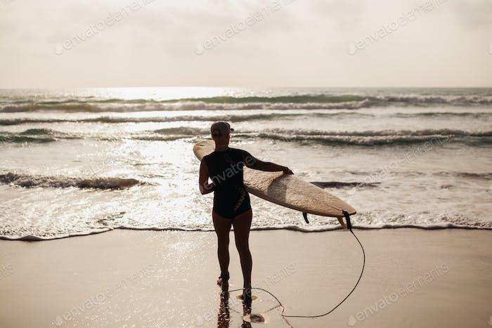 surf mujer con tabla de surf vista hacia atrás