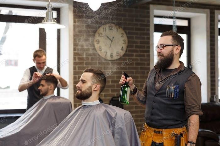 Mann bekommt Haarschnitt von Friseur im Friseurladen