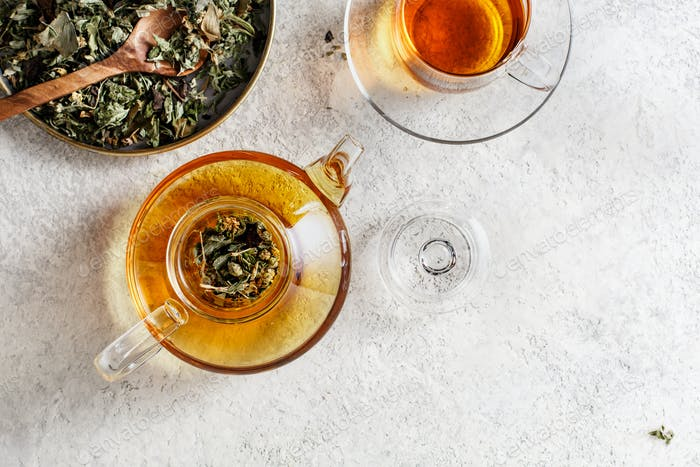 Glass teapot and a teacup with herbal tea