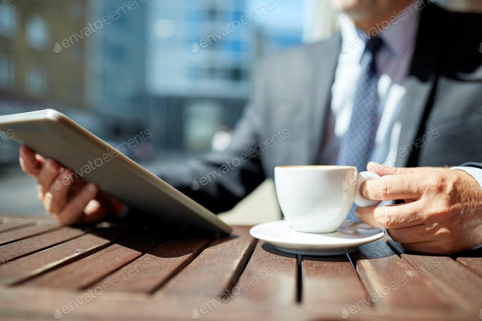 senior businessman with tablet pc and coffee
