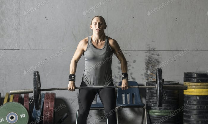 A strong young woman lifts a barbell in a gym, frontal view.