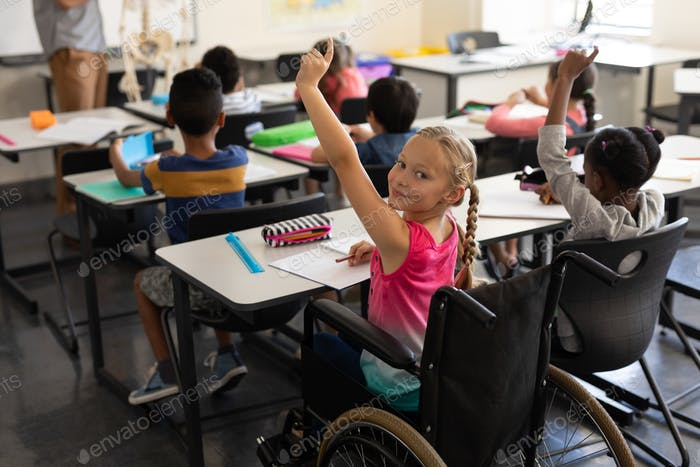 Smiling disable schoolgirl looking at camera and raising hand in classroom of elementary school