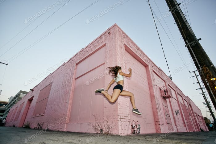 Female athlete running on sidewalk past pink building.