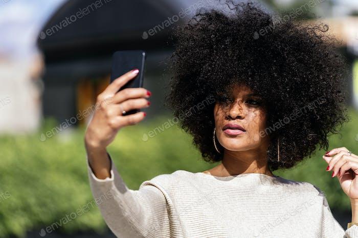 Portrait of attractive afro woman taking selfie portrait
