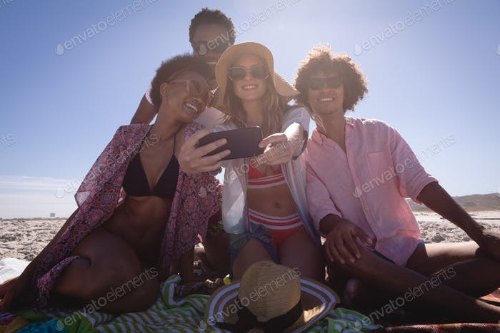 Group of diverse friends taking a selfie with mobile phone on the blanket at beach in the sunshine