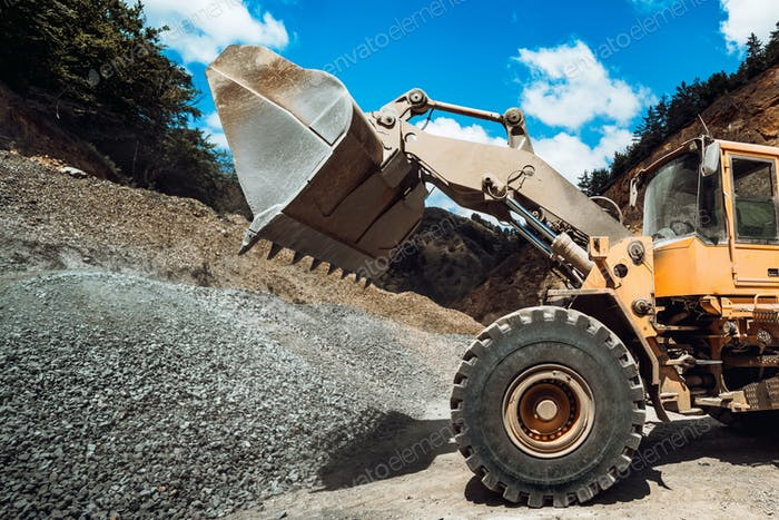 Heavy duty machinery loading gravel and transporting materials