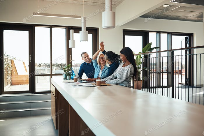 Business colleagues high fiving together during an office meeting