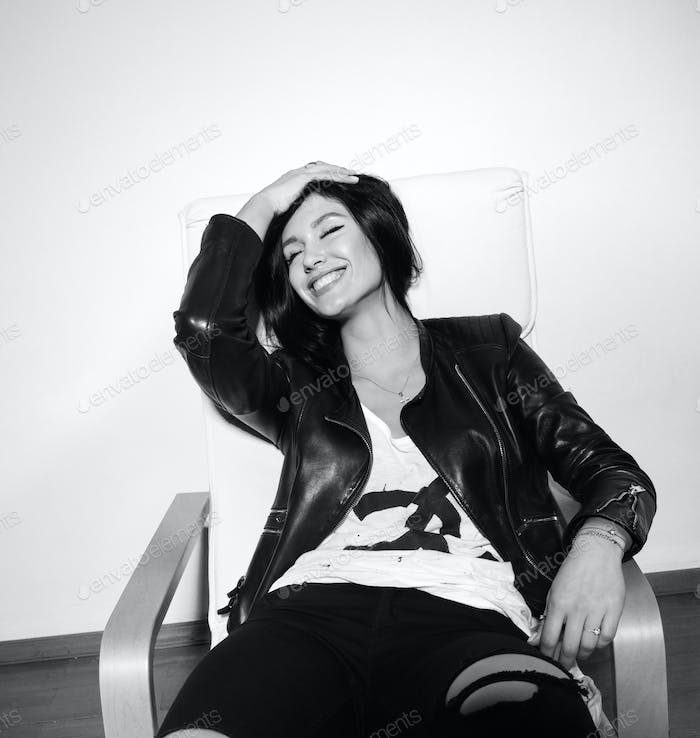 stylish smiling sexy brunette sitting on the chair and laughing