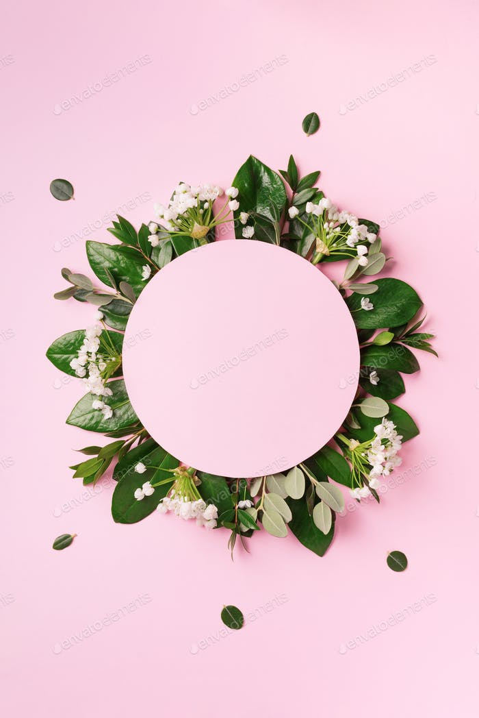 Creative layout made of green tropical leaves and white flowers on pink background. Top view. Flat