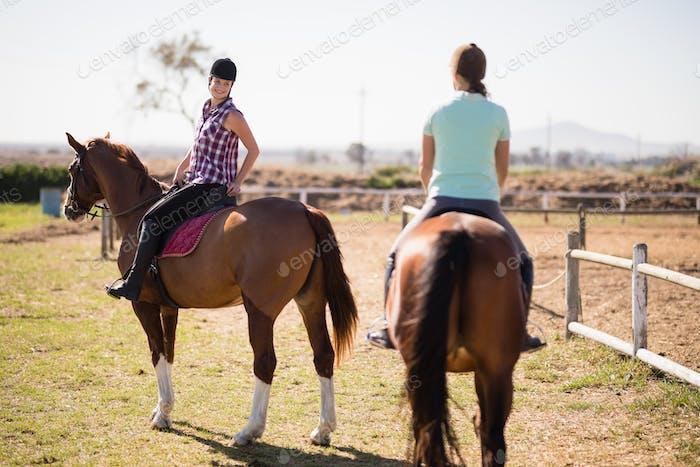 Female friends horseback riding on field