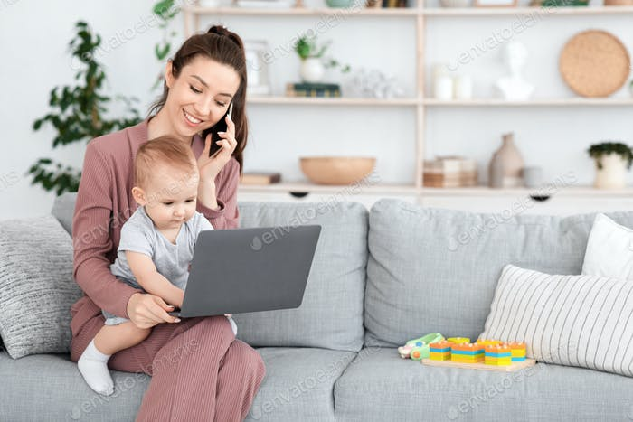 Working With Baby. Mom Talking On Cellphone While Toddler Typing On Laptop