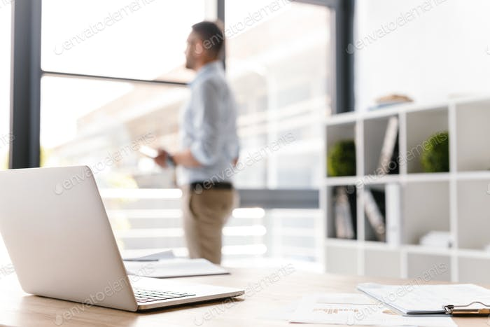 Photo of workplace with open white laptop lying on table, while
