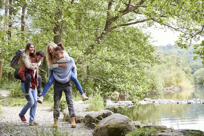 Four adult friends during a hike, men piggybacking their girlfriends